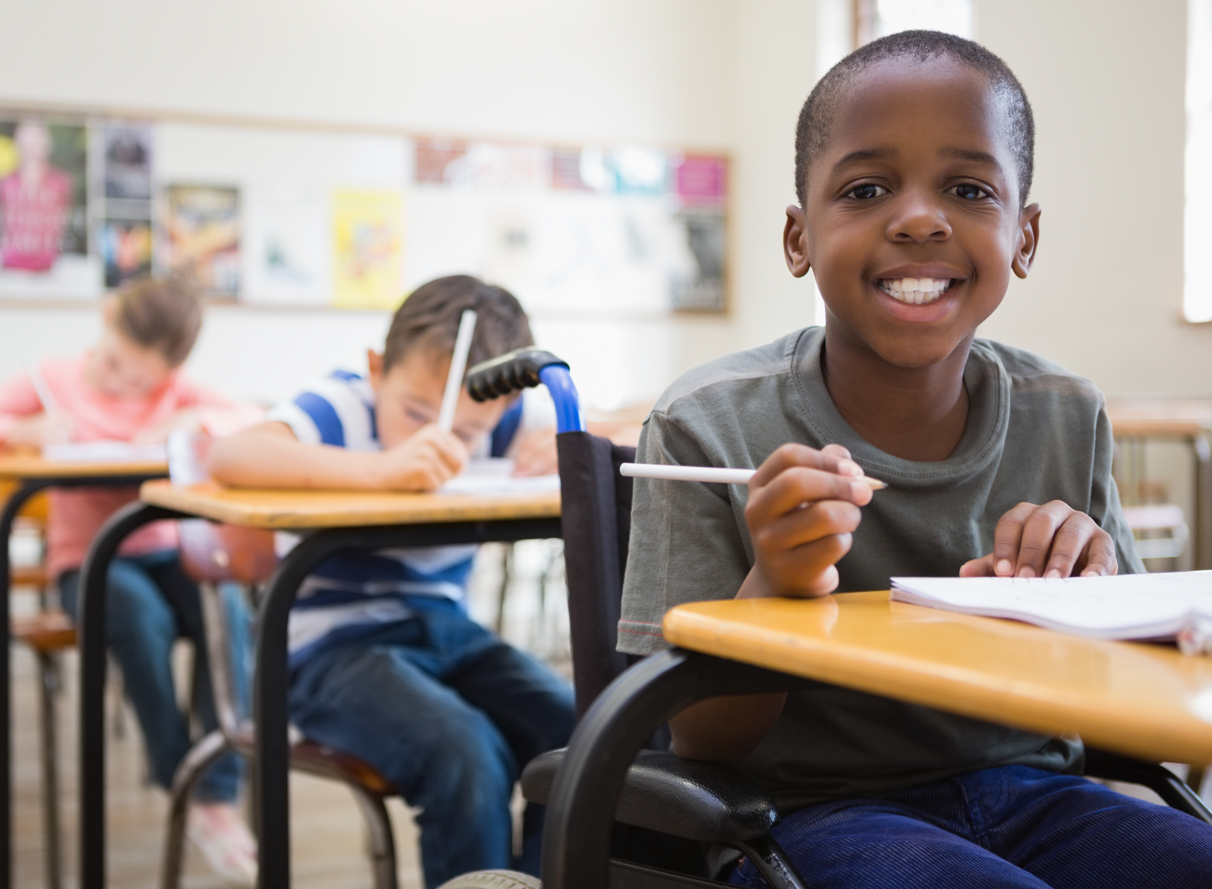A smiling boy sits in a classroom, writing in a notebook. He is using a wheelchair.