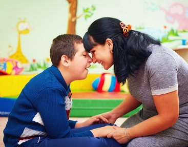 A boy with Cerebral Palsy is at therapy with his female caregiver. They are smiling and touching foreheads.