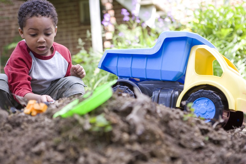 A toddler plays in the dirt in his backyard. Construction toys are in the foreground.